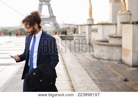 Attractive businessperson calling cooperator and disputing by phone with Eiffel Tower in background in. Young man making official journey to France. Concept of works debating and detached duty to Europe.