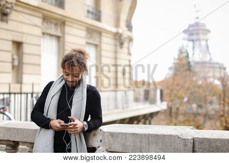 guy listening to music in white in ear headphones and new smartphone with Eiffel tower in background. Handsome raving boy has long fleecy hair and wears grey scarf with watch and black sweater. Concept of enjoying popular songs and tourist visiting Paris.