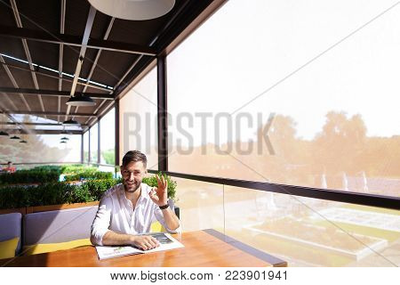 Satisfied magazine editor showing ok geste at cafe table. Personable man with beard wears classic style and looking at camera. Concept of glossy paper edition and writers career.