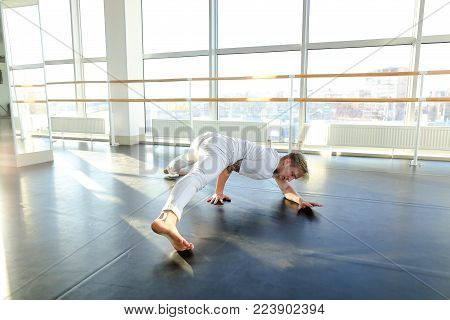 Gymnast train near ballet barre in sport gym, guy diligently doing stretching exercises for legs. Tattooed concentrated male wearing white sportswear sloping. Concept of well-equipped hall, sport clothes for men or individual workouts.