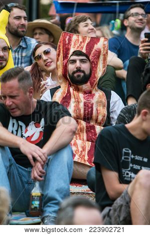ATLANTA, GA - OCTOBER 2017:  A man wears a bacon costume as he sits among a crowd of spectators waiting for the start of the Little Five Points Halloween parade in Atlanta, GA on October 21, 2017.