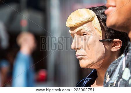 ATLANTA, GA - OCTOBER 2017:  A person wears a Donald Trump mask at the Little Five Points Halloween Parade in Atlanta, GA on October 21, 2017.