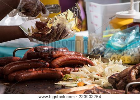 ATLANTA, GA - OCTOBER 2017:  A food vendor prepares to serve sausage, peppers and onions in foil as several sausages and vegetables cook on a grill at the Little Five Points Halloween parade on in Atlanta, GA October 21, 2017.