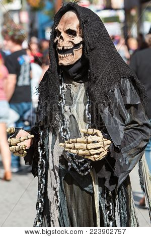 ATLANTA, GA - OCTOBER 2017:  A person dressed in black as the grim reaper walks through a crowd gathering to watch the Little Five Points Halloween Parade in Atlanta, GA on October 21, 2017.
