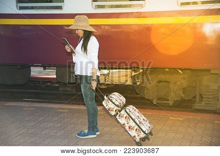 Pretty Asian Women Traveler Walk And Looking The Tablet Drag And Drop Luggage To The Train.