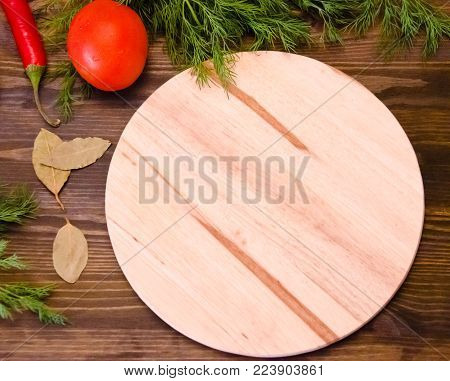 wooden brown background around the edges of the fennel, the tomatoes, the chili pepper Bay leaf spices, wooden cutting Board, selective focus