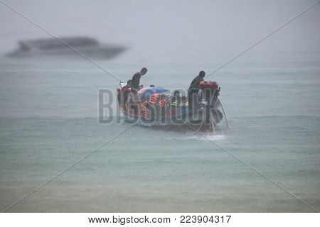 Tourist on the long tail boat with heavy rain in the sea. selective focus