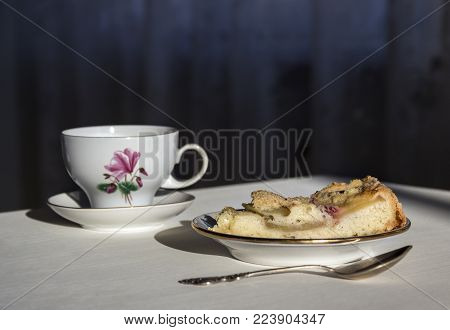 on the table a plate with a piece of apple pie, a spoon and a cup in the sunbeam