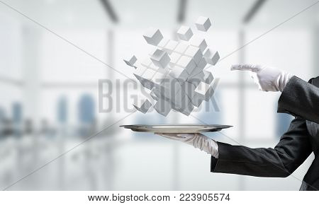 Cropped image of waiter's hand in white glove presenting multiple cubes on metal tray with office view on background. 3D rendering.