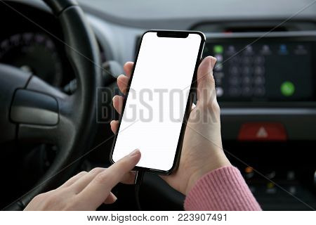 women hand holding phone with isolated screen in the car