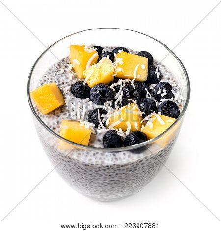 Chia pudding isolated in glass with blueberries, mango and shredded coconut.  Vegan superfood.