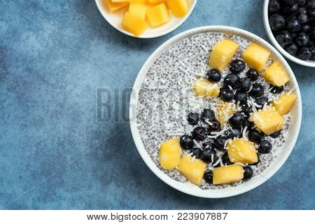 Chia seed pudding, top view, with blueberries, mango and coconut. Vegan superfood with almond milk.