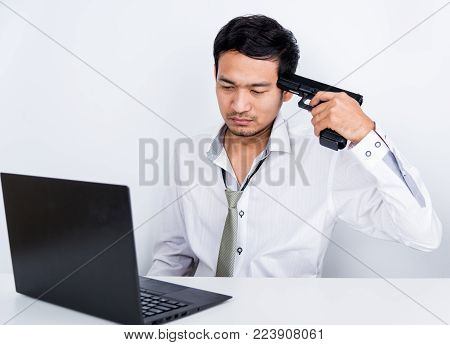Frustrated Young Man With Gun Point Mouth And Sitting At His Working Place