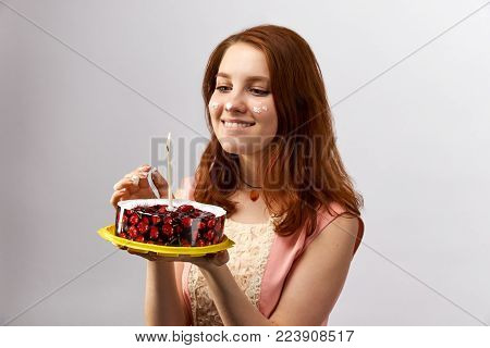 young attractive red-haired girl holding a cake with candle and makes a wish on the birthday. Her face covered in cream from the cake and sweets. Studio portrait on white background