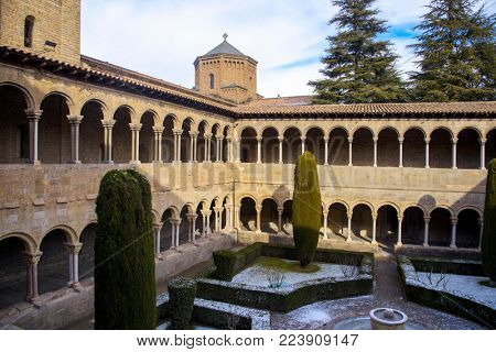 RIPOLL, SPAIN - DECEMBER 28, 2017: A view of the cloister of the medieval Monastery of Santa Maria de Ripoll, an important landmark in Catalonia, covered by the snow