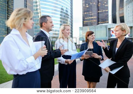 Employees of large corporation walking in   with tablet, laptop, notebook and document case. Concept of team members having break outside. Successful people dressed in classic wear style.