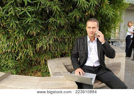 Male manager speaking by smartphone outdoors and working with laptop in  . Concept of modern technology, gadget and business  worker. Hardworking man wears black suit.