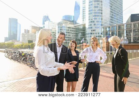 Prosperous business team rejoicing good result and greeting each other outdoors in  . Concept of enjoying win tender and employees of large organization. Happy satisfied partners smiling and greeting each other.