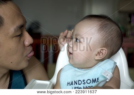 A father with tongue sticking out and his son is playing with each other
