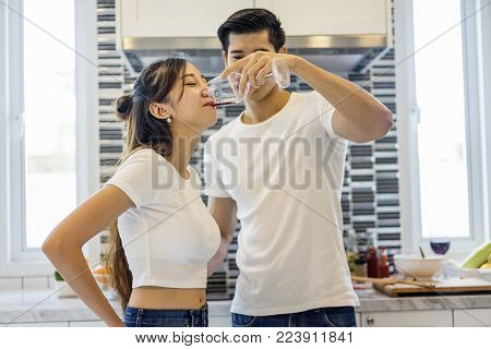 Beautiful asian young couple loving smiling is looking to cooking in kitchen at home, Happy handsome man feeding wine to her.
