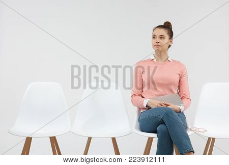 Confident successful young businesswoman holding digital tablet while waiting for meeting, sitting on chair