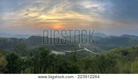 Mountain autumn panoramic landscape with colorful forest. Panorama of sunset in a mountain valley with wonderful gold light on a hills. Panoramic image of rural fields in evening light at Thailand