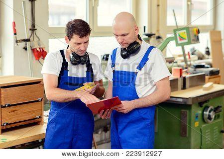 Two Worker In A Carpenter's Workshop In Conversation
