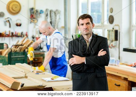 boss and worker together in a carpenter's workshop