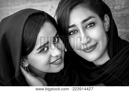 Iran, Persia, Isfahan - September 2016: beautiful local girls smiling at the old bridge in Esfahan. Black and white photo.