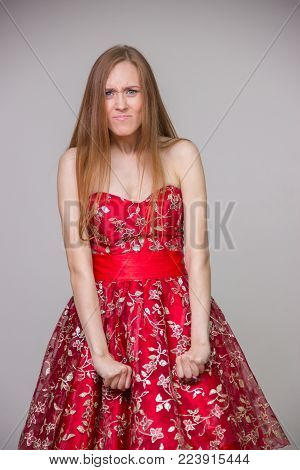 Beautiful young blond model in a red dress with an offended face on a white background