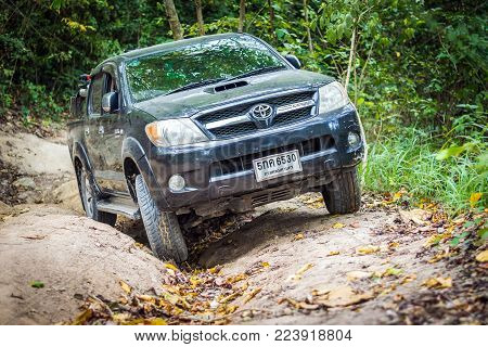 Chon Buri, Thailand-Dec 5, 2017: 4 wheel drive with a motorcycle on the tailgate is climbing on a difficult off-road in mountain forests in Thailand.