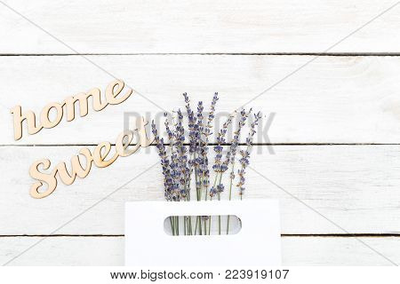 A bouquet of lavender and a wooden inscription sweet home. Flat lay