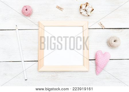 Square wooden frame and elements for design on a white wooden background. flat lay