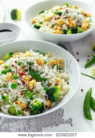 Fried rice with vegetables, broccoli, peas and eggs in a white bowl. soy sauce. healthy food.