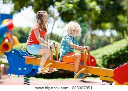 Kids climbing and sliding on outdoor playground. Children play in sunny summer park. Activity and amusement center in kindergarten or school yard. Child on colorful swing. Toddler kid outdoors.