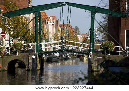 a old traditional green steel bridge bridging the Oude Rijn canal in the Dutch city of Leiden with a woman bicycling across the green bridge and canal. Leiden,The Netherlands September 29th 2017