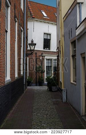 Leiden, The Netherlands - January 20th 2018 - The Schoolsteeg and Lokhorststraat with traditional Dutch houses with old Dutch rooftops with blue sky background and a little empty alley with plants and street lamps