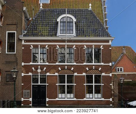 Leiden, The Netherlands - January 20th 2018 - A traditional old dutch house with windows a door and roof tiles front view at the Pieterskerkhof in Leiden