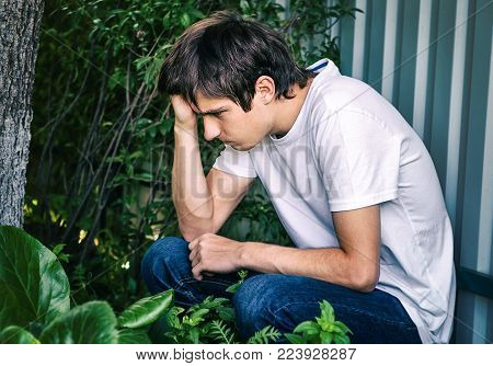 Toned Photo of Sorrowful Young Man sit outdoor