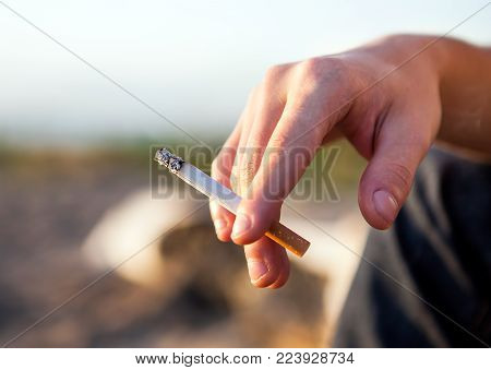 Person hold a Cigarette in the Hand outdoor closeup
