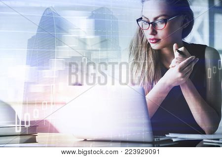 Portrait of beautiful young businesswoman using laptop at abstract workplace with forex chart and city view. Marketing and investment concept. Double exposure