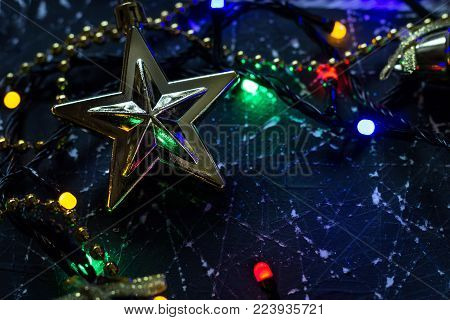 Christmas tree decoration in the shape of a star on a black and white background. The electric garland is included. Close-up