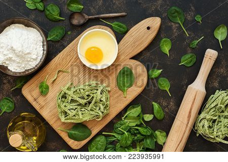 Preparation of pasta with spinach. Raw pasta on a cutting board, flour, eggs, spinach leaves on a capacious background. Top view.