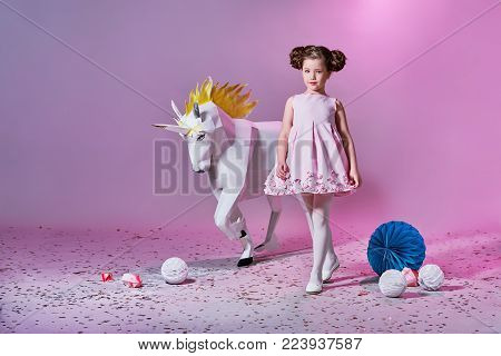 Fashion kid smiling. Designer collection. Origami and minimalism. White big unicorn origami made of paper. Romantic pretty girl in an elegant pink dress for teenage girls with a make-up. Fashion catalog clothes. Studio shot.