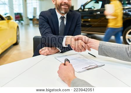 Close up of  client shaking hands with sales manager after signing purchase contract to buy new car in showroom