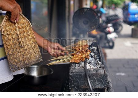 Satay making process. Satay or in Indonesian called sate is a dish of seasoned, skewered and grilled meat, served with a sauce.