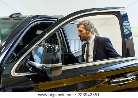 Portrait of handsome mature businessman getting into big luxury car in parking lot