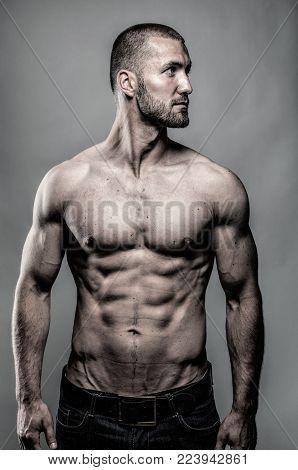 Handsome muscular sportsman standing in studio isolated
