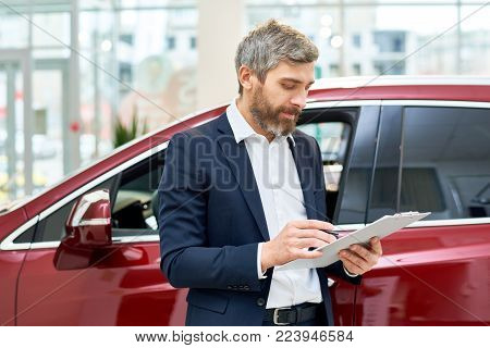 Portrait of handsome mature salesman making notes on clipboard  standing by brand new luxury car in showroom, copy space