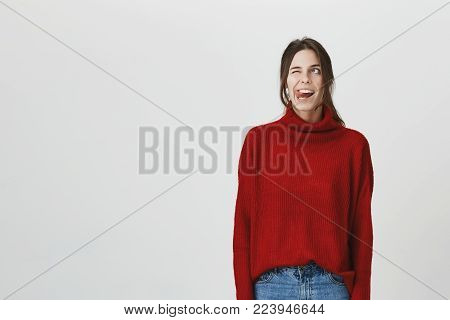 Portrait of funny positive dark-haired young female in red sweater and jeans with widely opened mouth, blinking, sticking out her tongue. Expressive european girl has fun indoors